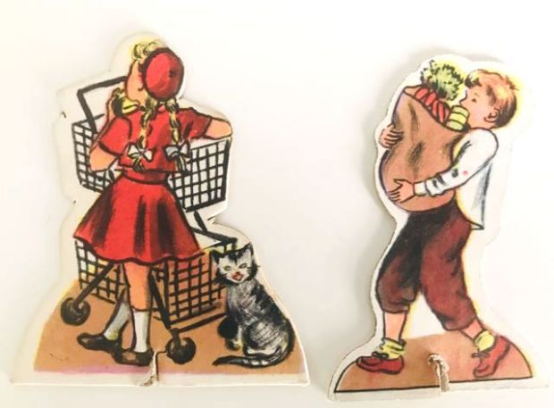 Two cardboard cut-outs: one showing girl and shopping trolley, the other a boy with a paper bag filled with vegetables.