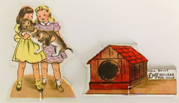 2 separate cardboard cut-outs. One depicting 2 girls carrying a dachshund, the other a doghouse with a for sale sign.
