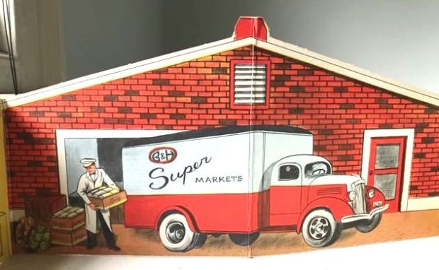 cardboard cutout showing man unloading van in front of warehouse.