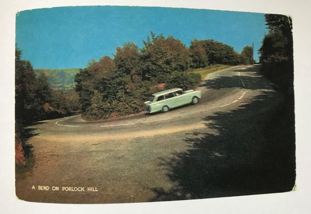 photo of a page from Martin Parr's 'Boring Postcards'. In colour. Car is driving around a bend.